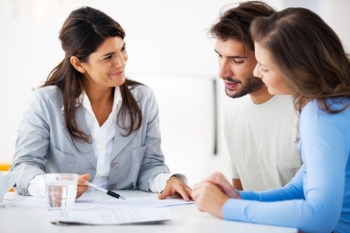 Couple looking at papers with real estate agent